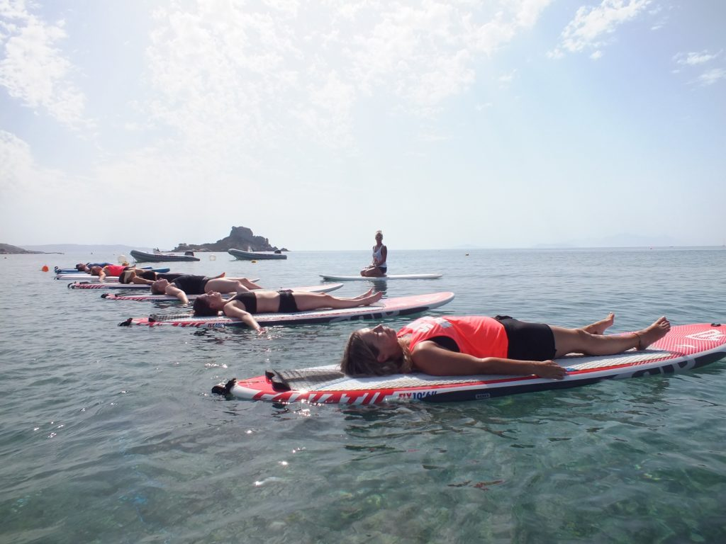 Yoga classes in the Aegean Sea, Kos. 8 ladies and an instructor, each on a paddleboard, lying down for a rest after a great lesson. The iconic Kastri Island lies in the background.