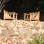 2 wooden armchairs under an old olive tree in the garden, on a dry stone wall terrace