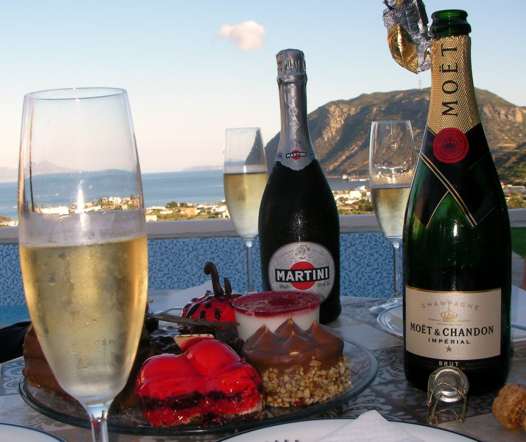 A table is laden with bottles of champagne, glasses half filled, and celebratory cakes are waiting to be eaten. The table is laid by the pool at The Tower House, with the sea and mountains in the background.