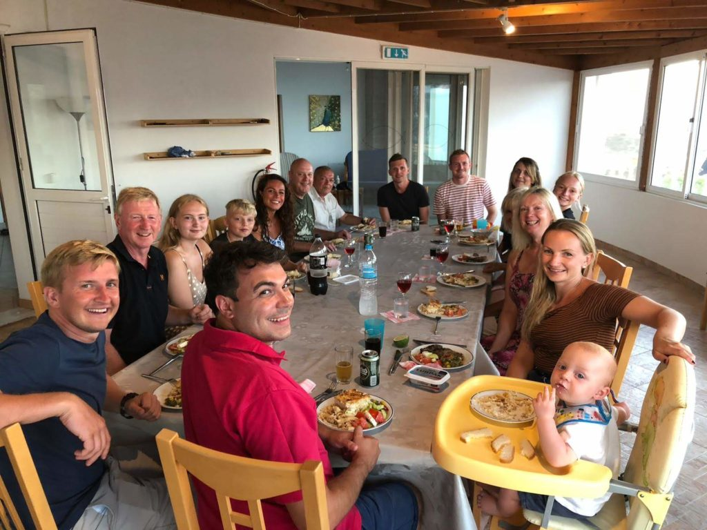 A happy group of friends and families share a meal in the large dining room at The Tower House in Kos