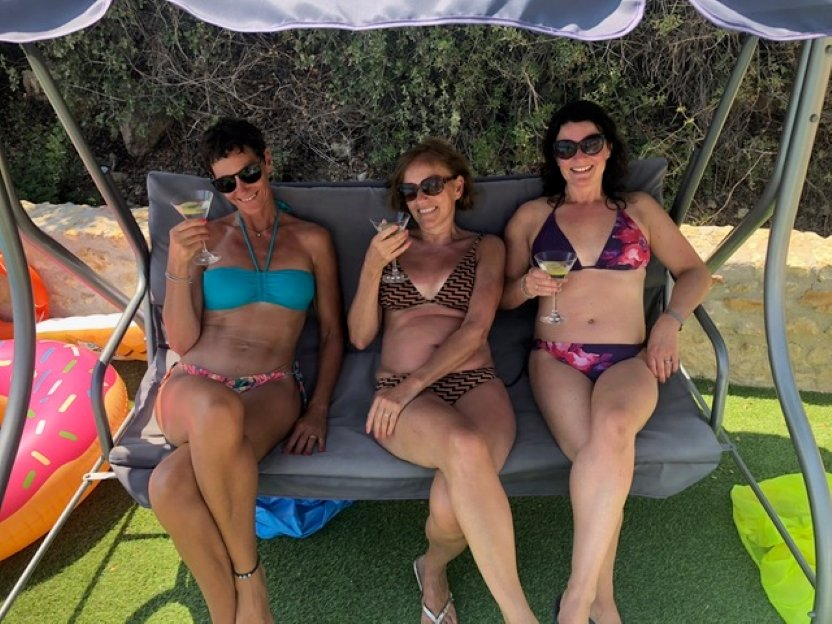 3 ladies on the swing seat enjoy cocktails by the pool