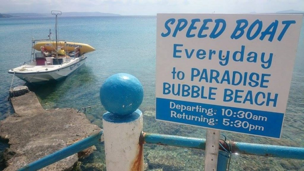 The sign advertising the speedboat trips to Paradise beach